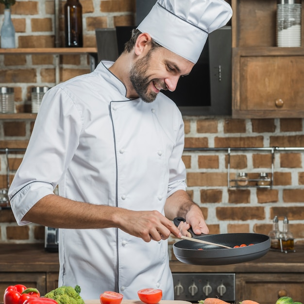 Male chef's preparing food in the frying pan Free Photo