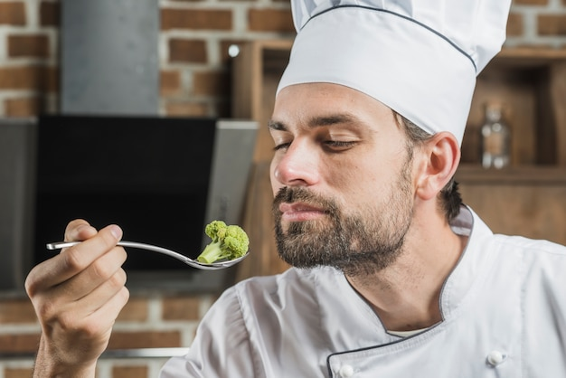 Male chef smelling broccoli in stainless steel spoon Free Photo