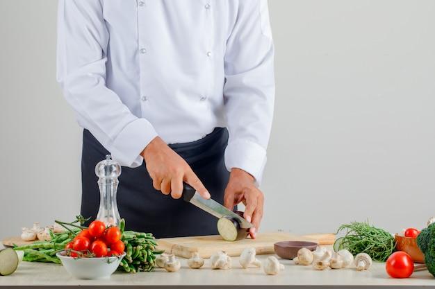 Cuoco unico maschio in uniforme e grembiule che tagliano melanzana a pezzi sul bordo di legno in cucina Foto Gratuite