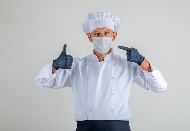 Cuoco unico maschio in uniforme, grembiule e cappello che mostrano maschera e pollici in su e che sembrano attenti Foto Gratuite