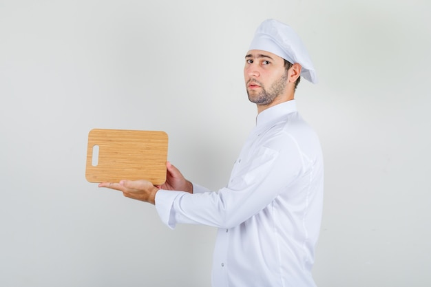 Male chef in white uniform holding wooden cutting board and looking strict Free Photo