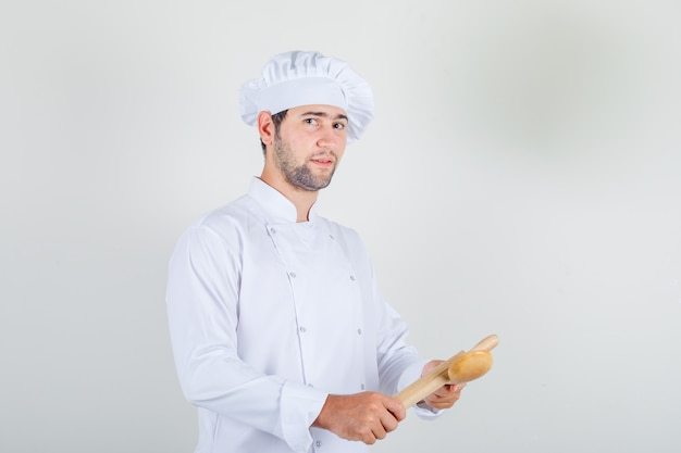 Male chef in white uniform holding wooden spoon and rolling-pin Free Photo