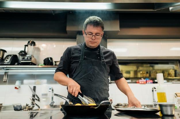 Cuoco unico maschio con il grembiule che cucina la pasta Foto Gratuite