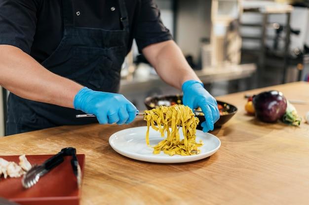 皿にパスタを置く手袋を持つ男性シェフ 無料写真