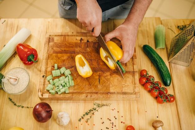 ナイフで男性シェフが木の板に黄色の唐辛子をカットします。 Premium写真