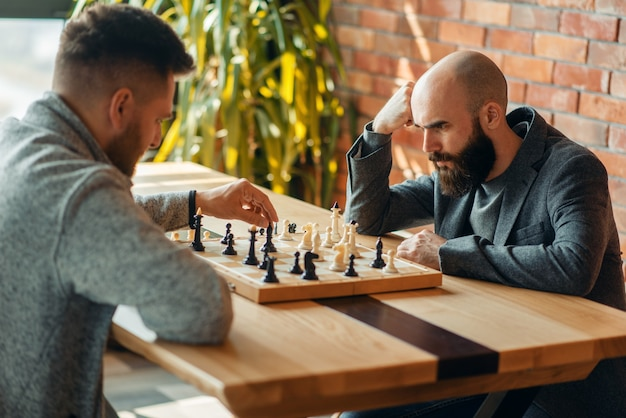ボードで遊ぶ男性のチェスプレーヤーは、黒い象を移動します。 Premium写真