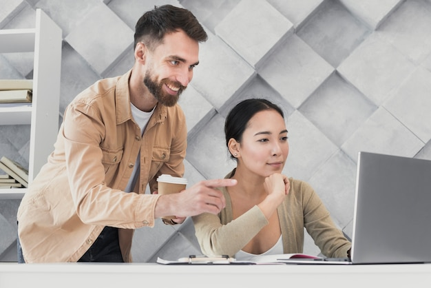 Male colleague pointing at laptop Free Photo