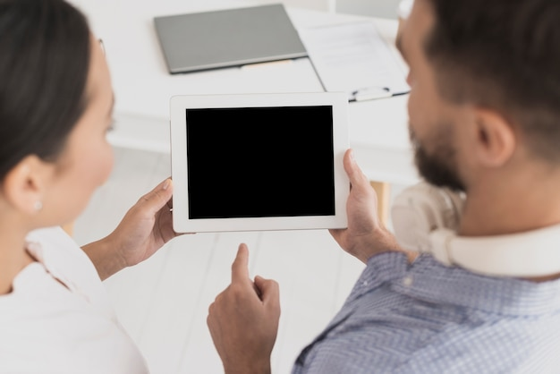 Male colleague showing tablet to female colleague Free Photo