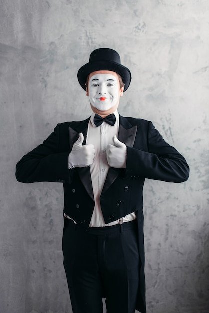 Male comedy artist posing, pantomime with white makeup mask. Premium Photo