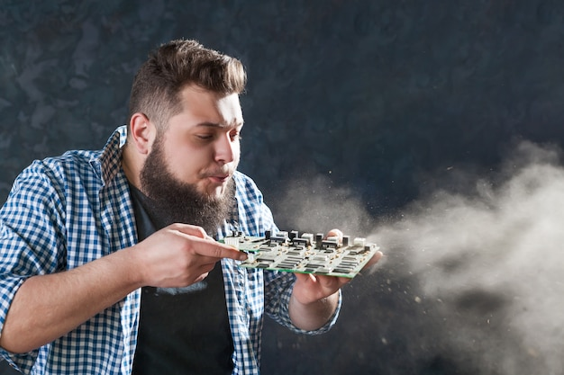 Male computer engineer blows off the dust from motherboard. electronic devices repairing technology and service support Premium Photo