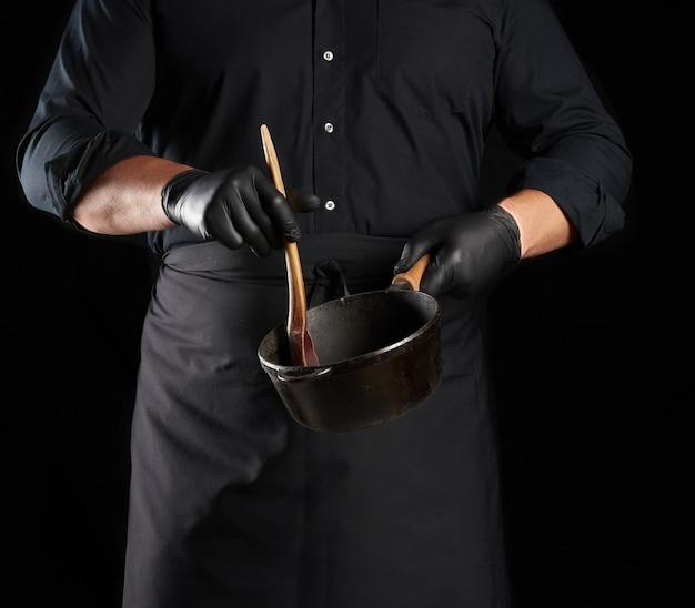 黒のユニフォームとラテックスの手袋をはめた男性料理人が空の丸いヴィンテージ黒鋳鉄鍋を保持 Premium写真