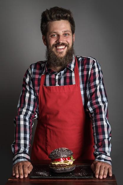 新鮮な自作の黒いハンバーガーの近くに立って笑っている赤いエプロンの男性料理人 Premium写真