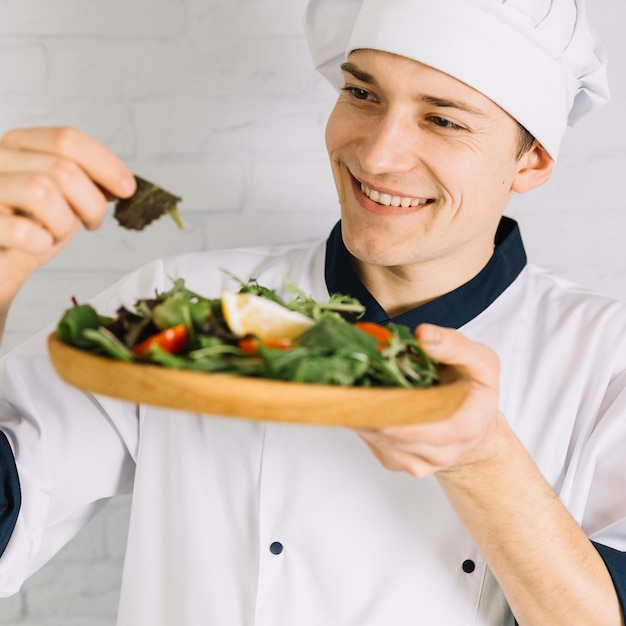 Male cook looking at wooden plate with salad Free Photo