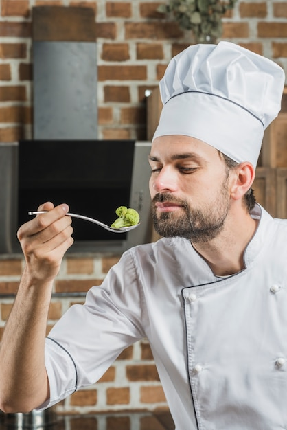 Male cook smelling green broccoli in spoon Free Photo
