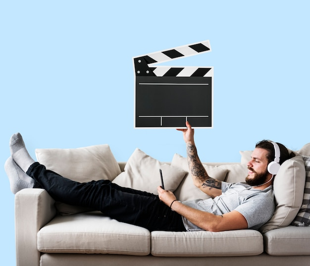 Male on a couch holding a clapper icon Free Photo