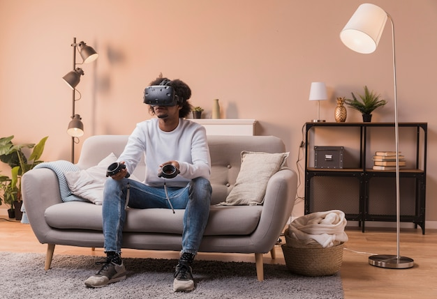 Male on couch with virtual headset Free Photo