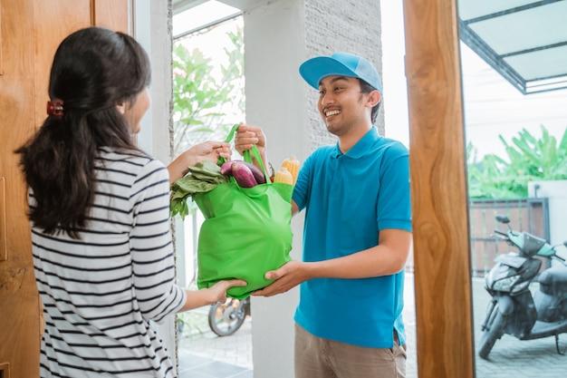 Мужской курьер доставляет продукт покупателю Premium Фотографии