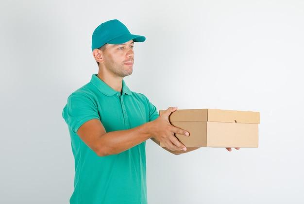 Corriere maschio in maglietta verde con cappuccio che consegna scatola di cartone Foto Gratuite