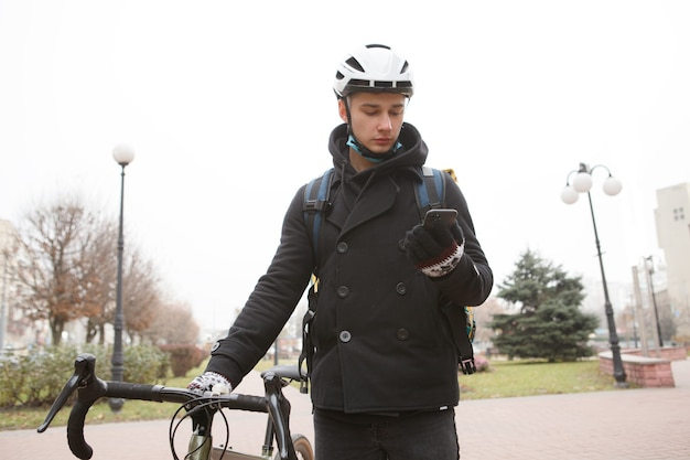 市内を自転車で歩くスマートフォンを使用する男性宅配便 Premium写真