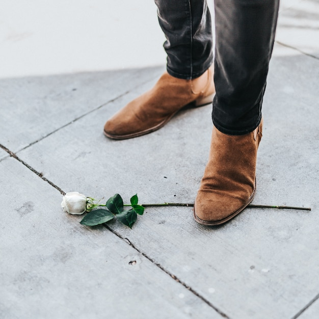 Male in cowboy boots standing on a single white rose branch Free Photo