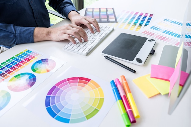 Male creative graphic designer working on color selection and color swatches Premium Photo