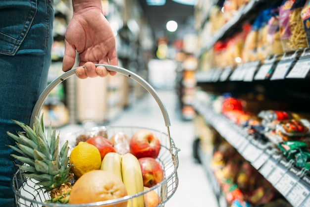 果物のバスケット、スーパーマーケットで食品を選択する人々と男性客の手。食料品店でのショッピング Premium写真