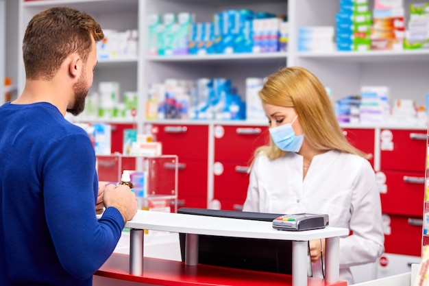 약국에서 약제사와 별개의 이야기를하는 남성 고객 프리미엄 사진