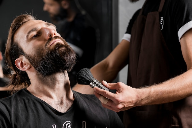 Male customer with beard near hairdresser holding shaving brush Free Photo