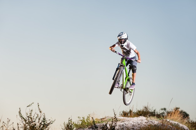 Male cyclist flying on a mountain bike over the top of the mountain against blue sky. Premium Photo
