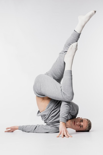 Танцовщица в носках и спортивном костюме позирует с поднятыми ногами Бесплатные Фотографии