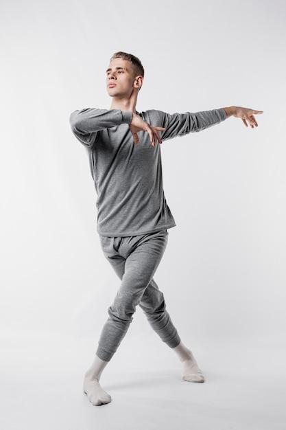 Танцовщица в спортивном костюме и носках дает позу балета Бесплатные Фотографии