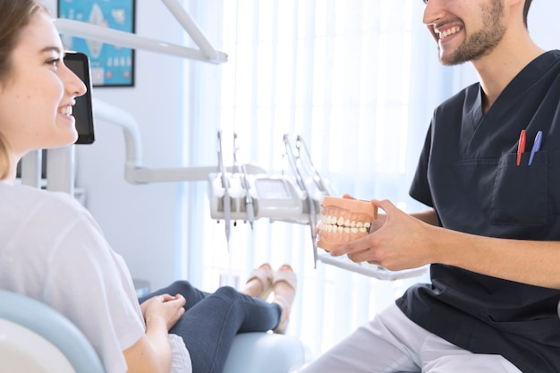 Male dentist explaining patient holding teeth model in clinic Premium Photo