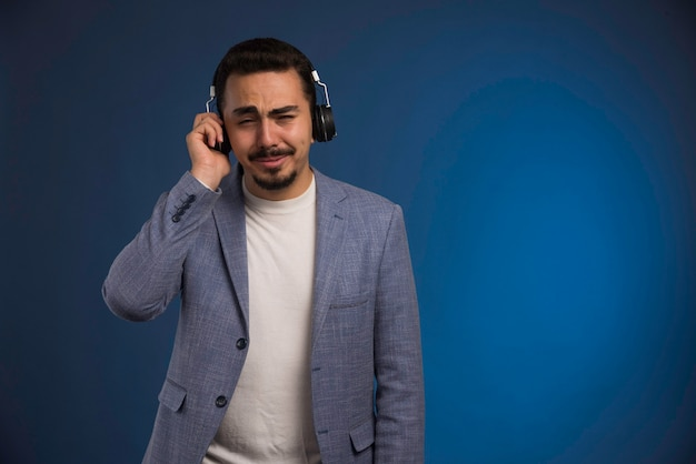 Male dj in grey suit listening to headphones and gets touched. Free Photo