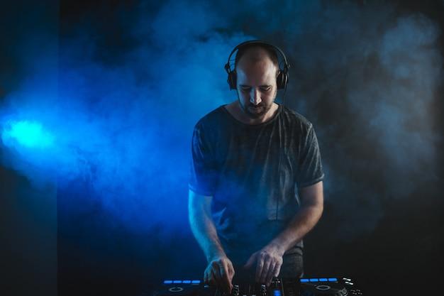 Мужской ди-джей, работающий под синими огнями и дымом в студии на фоне темноты Бесплатные Фотографии