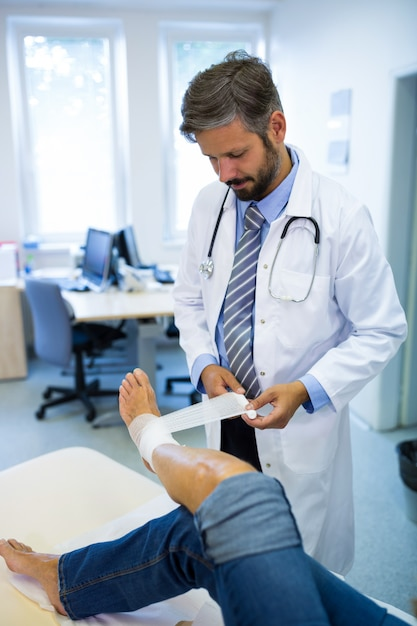 Male Doctor Bandaging Foot Of Female Patient Photo  Free -2116
