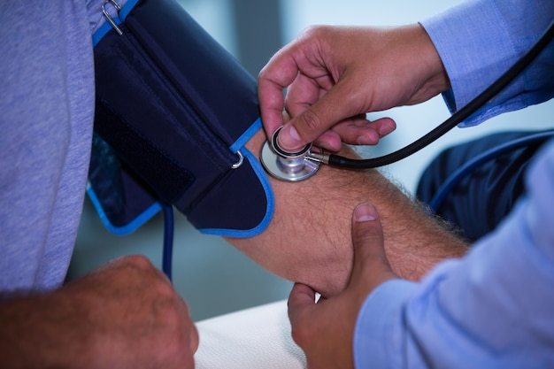 Male doctor checking blood pressure of patient Free Photo