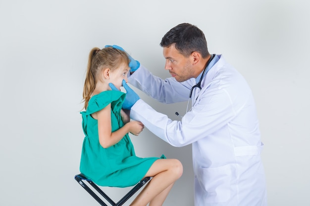 Male doctor examining little girl's eyes in white uniform, gloves and looking careful Free Photo