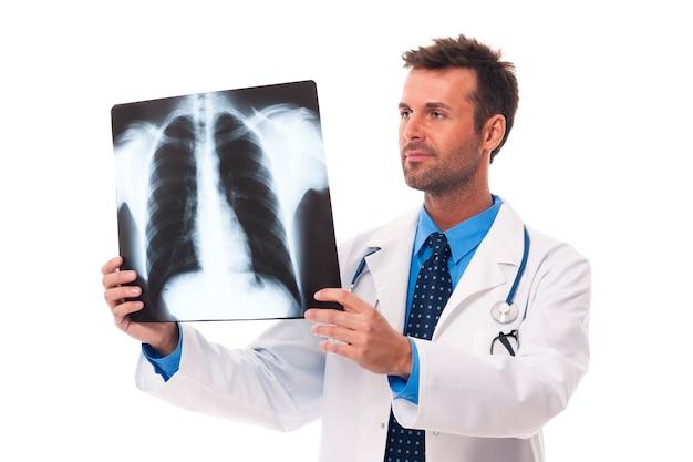 Medico maschio che esamina l'immagine dei raggi x Foto Gratuite
