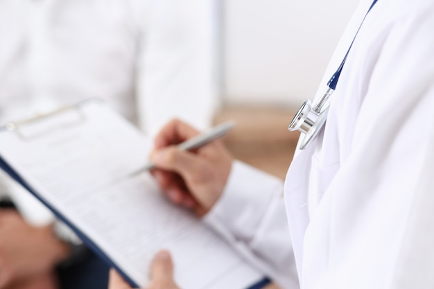 Male doctor hand hold silver pen filling patient history list Premium Photo