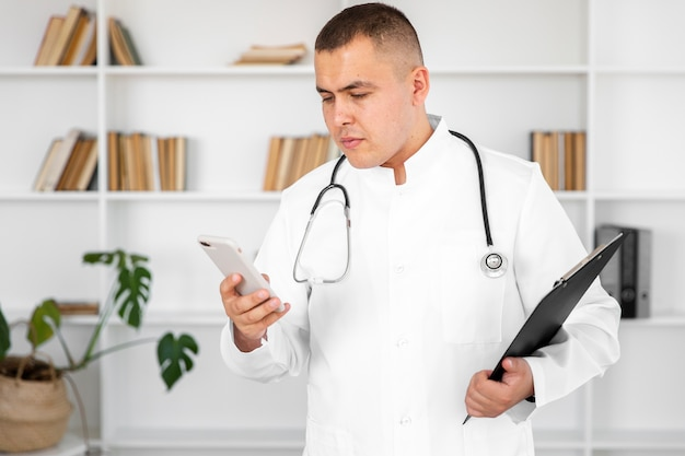 Male doctor holding a phone and a clipboard Free Photo