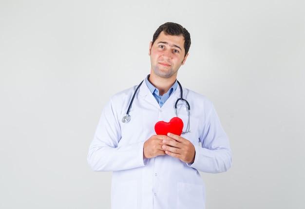 白衣で赤いハートを保持し、希望を探している男性医師 無料写真
