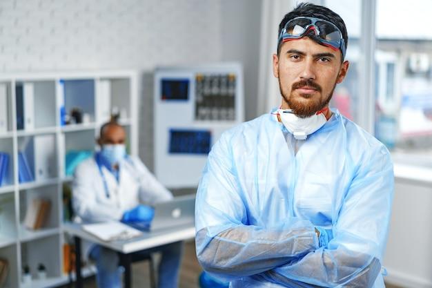 병원 캐비닛에 서 보호 의료 가운에 남성 의사 초상화 프리미엄 사진