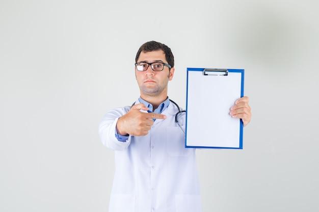 白衣を着た男性医師、クリップボードに指を指し、真剣に見える眼鏡 無料写真