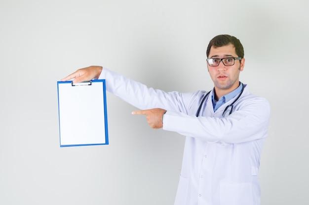 白衣を着た男性医師、クリップボードに指を指している眼鏡 無料写真