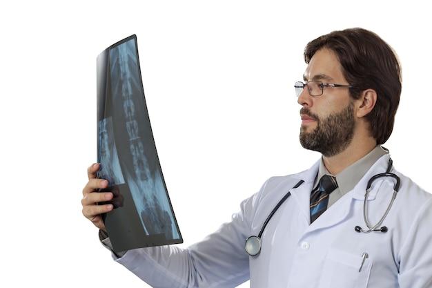 Medico maschio che esamina una radiografia su uno spazio bianco. Foto Gratuite
