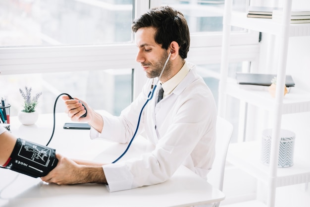 Male doctor measuring blood pressure of patient in clinic Free Photo
