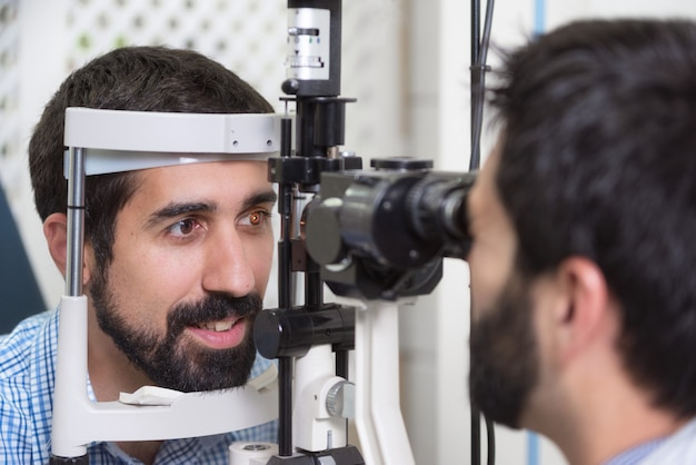 Male doctor ophthalmologist is checking the eye vision of handsome young man in modern clinic Premium Photo