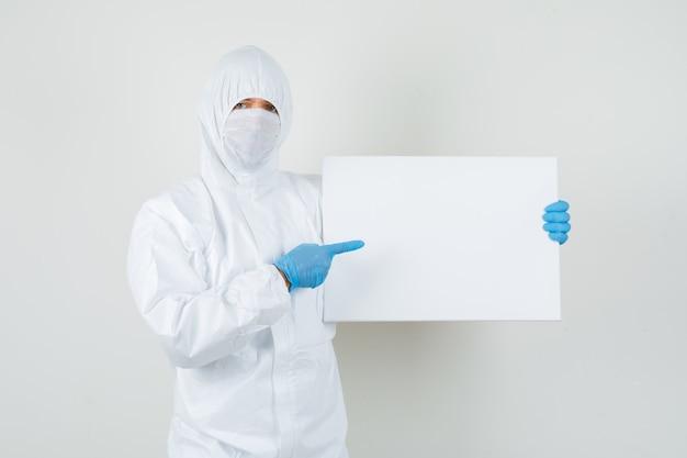 Medico maschio che indica alla tela bianca in tuta protettiva Foto Gratuite