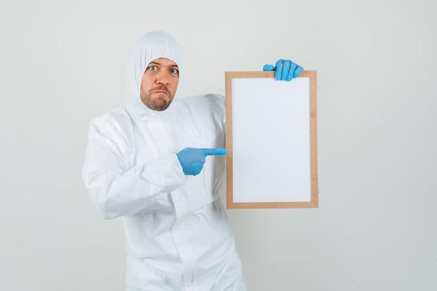 Medico maschio che indica al telaio vuoto in tuta protettiva Foto Gratuite
