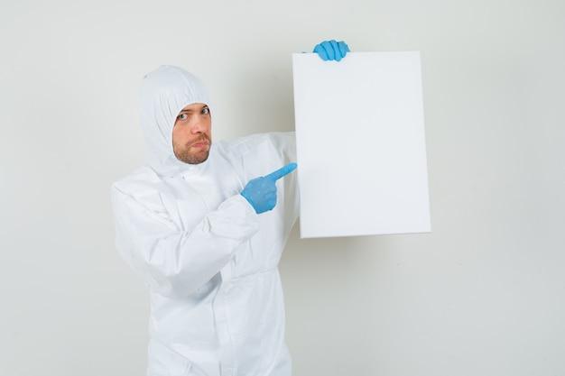 Medico maschio che indica alla tela vuota in tuta protettiva Foto Gratuite